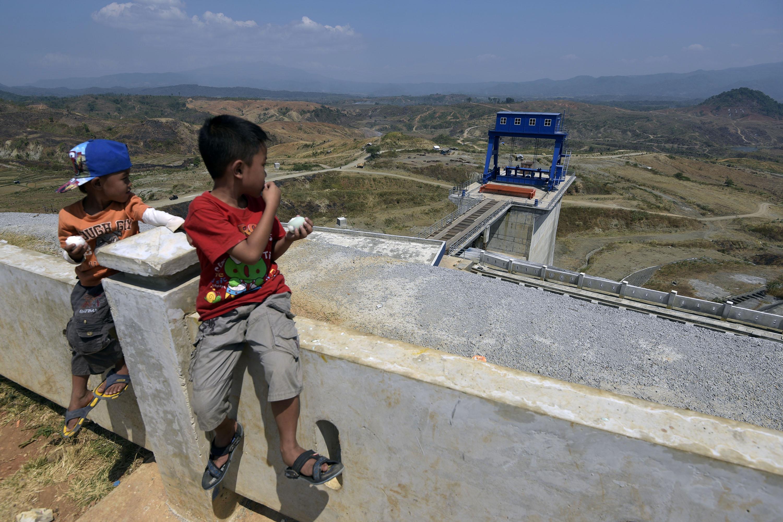 Dua anak melihat Waduk Jatigede yang belum tergenang air di Sumedang, Jawa Barat, Sabtu (1/8). Penggenangan waduk yang direncanakan akan dilakukan pada 1 Agustus 2015 akhirnya ditunda karena proses pembayaran dana ganti rugi kepada warga yang bermukim di area genangan tersebut belum selesai yakni baru sekitar 3.000 bidang tanah yang sudah terbayar dari sekitar 11.000. ANTARA FOTO/Sigid Kurniawan/ed/foc/15.
