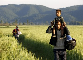 Seorang imigran Afghanistan membawa putranya, diikuti oleh istrinya saat mereka berjalan melewati sebuah ladang di dekat perbatasan Yunani-Makedonia dari desa perbatasan Idomeni di prefektur Kilkis, Yunani. Reuters/Yannis Behrakis