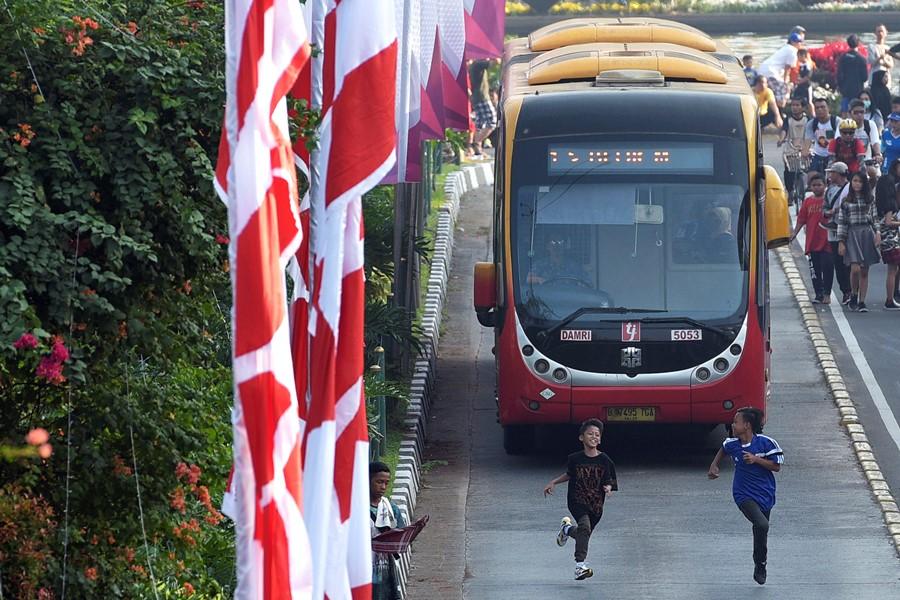 Dua anak berlari di jalur bus Transjakarta saat sebuah bus melintas di Jalan MH Thamrin, Jakarta, Minggu (16/8). Aksi tersebut dapat membahayakan keselamatan jiwa dari para pengguna jalan dan menghambat operasional bus Transjakarta. ANTARA FOTO/Sigid Kurniawan