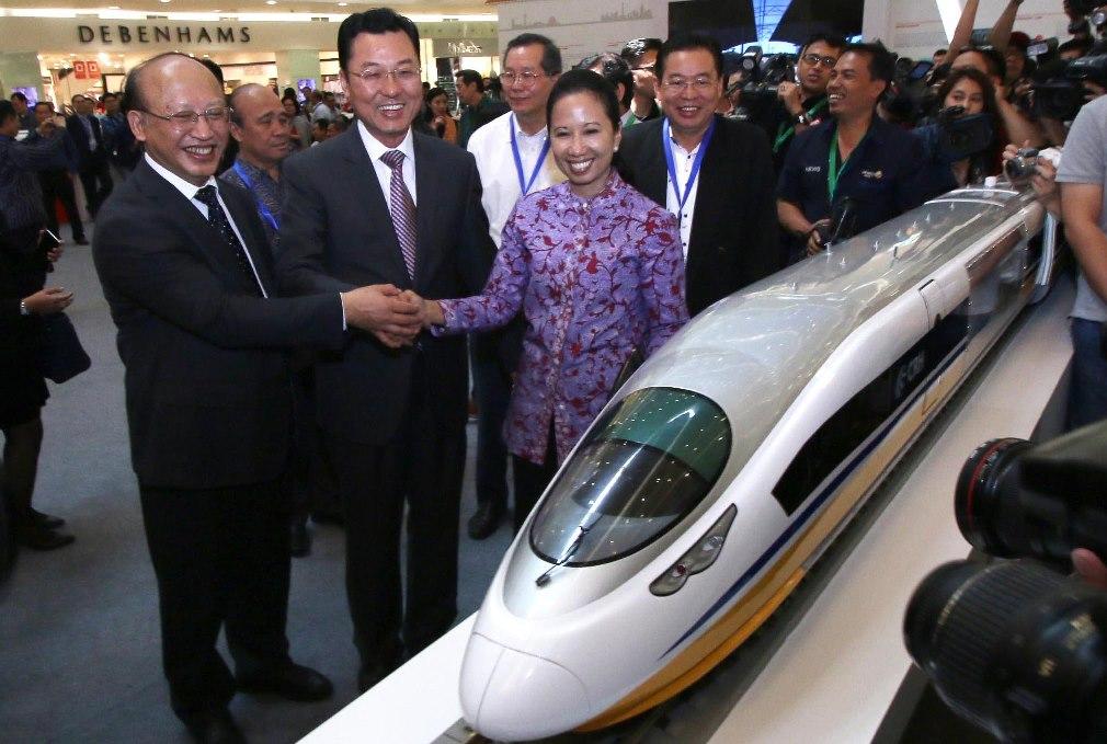 Menteri BUMN Rini Soemarno (ketiga kiri), Dubes China untuk Indonesia Xie Feng (kedua kiri), CRW Chief Engineer He Huawu (kiri), dan Managing Director Sinar Mas G. Sulistiyanto (kanan) berjabat tangan usai pembukaan Pameran Kereta Cepat dari Tiongkok di Jakarta, Kamis (13/8). ANTARA FOTO/Rivan Awal Lingga