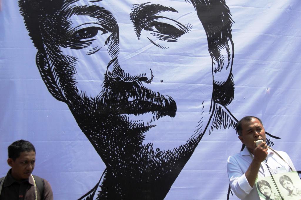 Warga yang menamakan diri Masyarakat Sipil Aceh berorasi di depan baliho dan poster Munir saat aksi unjukrasa di Simpang Lima, Banda Aceh, Senin (7/9). Masyarakat Sipil Aceh mendesak Presiden Joko Widodo mengusust kasus pelanggaran HAM atas kematian Munir dan membentuk undang-undang Komisi Kebenaran dan Rekonsiliasi (KKR). ANTARA FOTO/Ampelsa/nz/15