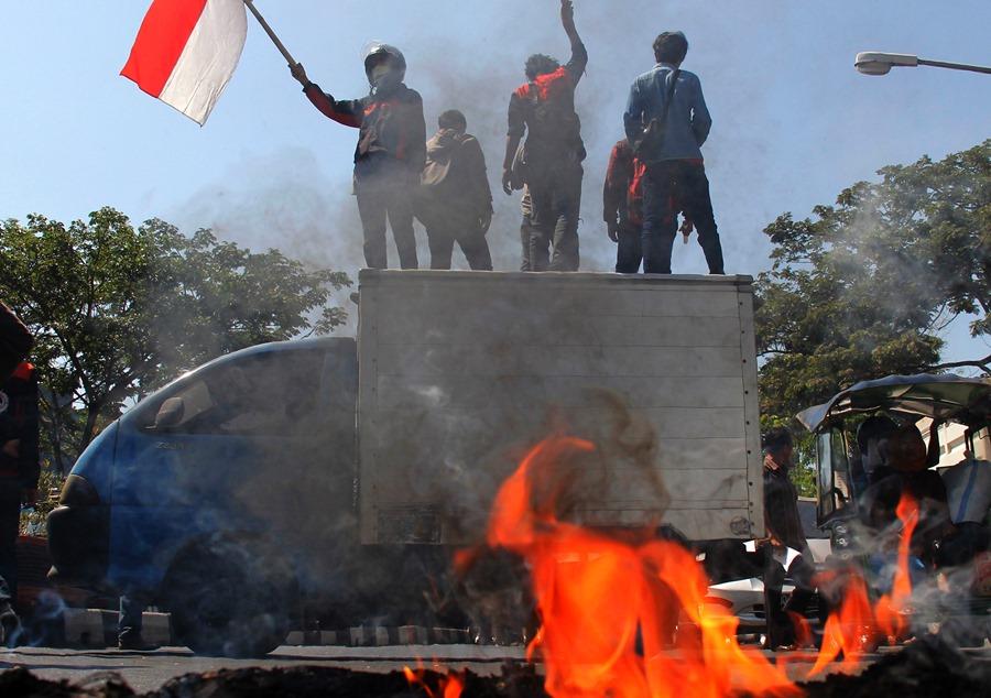 Mahasiswa yang tergabung dalam Pro Demokrasi Mahasiswa membakar ban bekas saat berunjuk rasa di depan kampus Universitas Muhammadiyah (Unismuh) Makassar, Sulawesi Selatan, Kamis (17/9). Dalam aksi tersebut mereka mendesak pemerintah agar serius mengatasi darurat asap dan penegakan hukum terhadap perusahaan pembakaran lahan. ANTARA FOTO/Abriawan Abhe