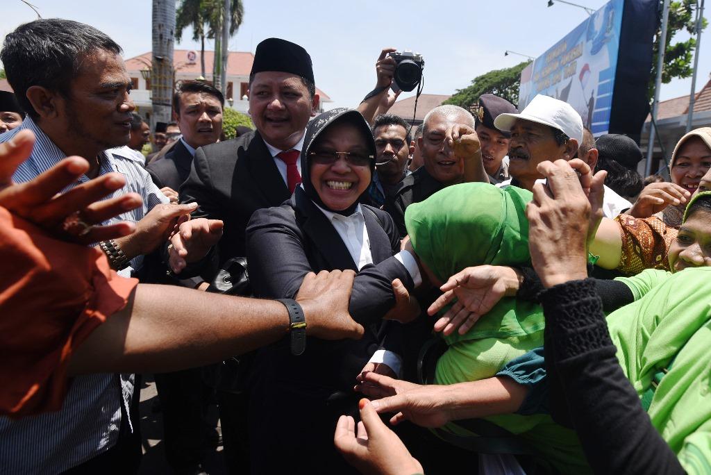 Mantan Walikota Surabaya Tri Rismaharini (tengah) menyalami sejumlah ibu rumah tangga yang menggelar aksi di depan Gedung Negara Grahadi Surabaya, Jawa Timur, Senin (28/9). Aksi tersebut sebagai bentuk rasa terima kasih kepada Tri Rismahari yang telah memimpin kota Surabaya dan sekaligus bentuk dukungan kepadanya. ANTARA FOTO/Zabur Karuru/aww/15.