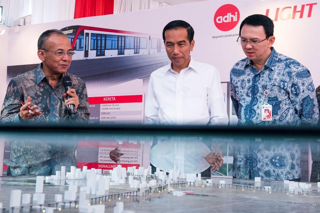 Presiden Joko Widodo (tengah) didampingi Gubernur DKI Jakarta Basuki Tjahaja Purnama (kanan) mendengarkan penjelasan maket proyek pembangunan Light Rail Transit (LRT) dari Direktur Utama Adhi Karya Kiswodarmawan (kiri) pada Groundbreaking Light Rail Transit (LRT) Indonesia di Jakarta, Rabu (9/9). LRT merupakan salah satu moda transportasi massal berbasis rel yang ramah lingkungan dan pembangunannya dilakukan secara elevated di atas tanah ruang milik jalan tol dan non tol serta direncanakan akan selesai pada tahun 2018. ANTARA FOTO/M Agung Rajasa/ama/15.