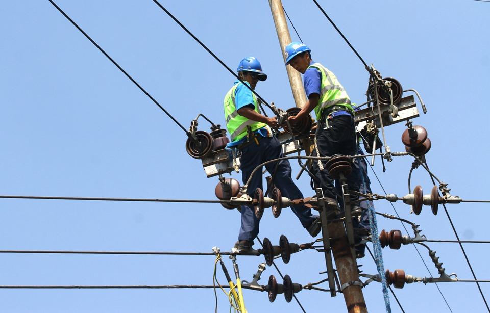 Pekerja memperbaiki jaringan listrik yang kelebihan beban di kawasan pemukiman di jalan Diponegoro, Batu, Jawa Timur, Selasa (8/9). ANTARA FOTO/Ari Bowo Sucipto