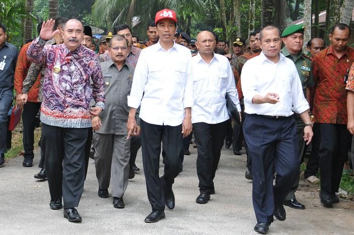 Presiden Jokowi (tengah) berjalan bersama Menteri Desa Marwan Jafar (ketiga kanan) usai melakukan peletakan batu pertama pembangunan sejumlah infrastruktur di Nagari Parit Malintang, Kecamatan Enam Lingkung, Kabupaten Padang Pariaman, Kamis (8/10). ANTARA FOTO