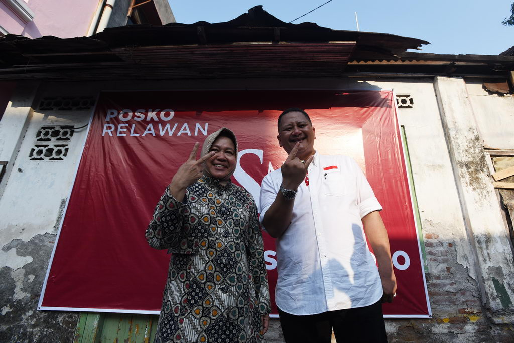 Pasangan calon Wali Kota dan Wakil Wali Kota Surabaya Petahana, Tri Rismaharini (kiri) dan Whisnu Sakti Buana (kanan) berpose sambil menunjukkan dua jari ketika peresmian posko relawan pertama di kampung Kebangsren II, Surabaya, Jawa Timur, Jumat (2/10). Tim pemenangan Risma-Wisnu menargetkan 50 ribu posko relawan di 5.000 RT yang ada di Surabaya. ANTARA FOTO/Zabur Karuru/ama/15