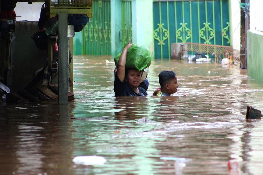 Warga berjalan menembus banjir yang melanda kawasan Kampung Pulo, Jakarta, Senin, (16/11). Kawasan di sepanjang aliran Kali Ciliwung terendam banjir akibat Bendungan Katulampa yang sudah mencapai siaga satu. ANTARA FOTO/M Ali Wafa