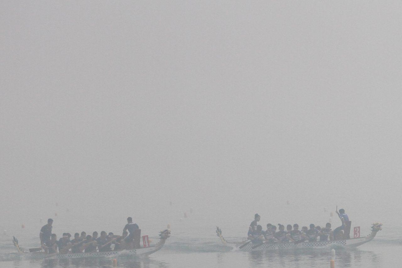 Sejumlah tim perahu naga beradu kecepatan untuk menjadi yang terbaik di danau ski air Jakabaring Sport City (JSC) yang tertutup kabut asap kejuaraan Asian Canoe Championship 2015, Palembang, Sumsel, Minggu (8/11). Hal ini membuat sejumlah atlet sempat mengalami kesulitan dikarenakan jarak pandang yang minim saat berlomba. ANTARA FOTO/Nova Wahyudi/ama/15