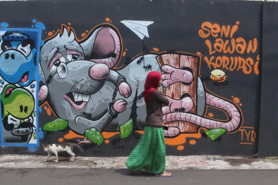 Seorang warga melintasi mural anti korupsi berjudul 'Seni Lawan Korupsi' di kawasan Kebon Nanas, Jakarta, Senin (09/11). Karya seni tersebut mewakili suara masyarakat yang mencerminkan dukungan terhadap pemberantasan korupsi. ANTARA FOTO