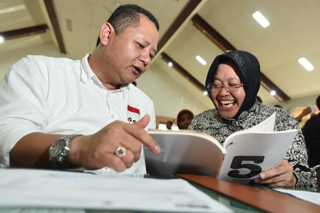 Calon Walikota Surabaya Tri Rismaharini (kanan) dan pasangannya calon Wakil Walikota Surabaya Wisnu Sakti Buana (kiri) membaca buku yang dibagikan KPK ketika mengikuti pembekalan dan deklarasi calon kepala daerah dan penyelenggara Pilkada Jatim di Unesa, Surabaya, Jawa TImur, Kamis (12/11). ANTARA FOTO/Zabur Karuru/aww/15.