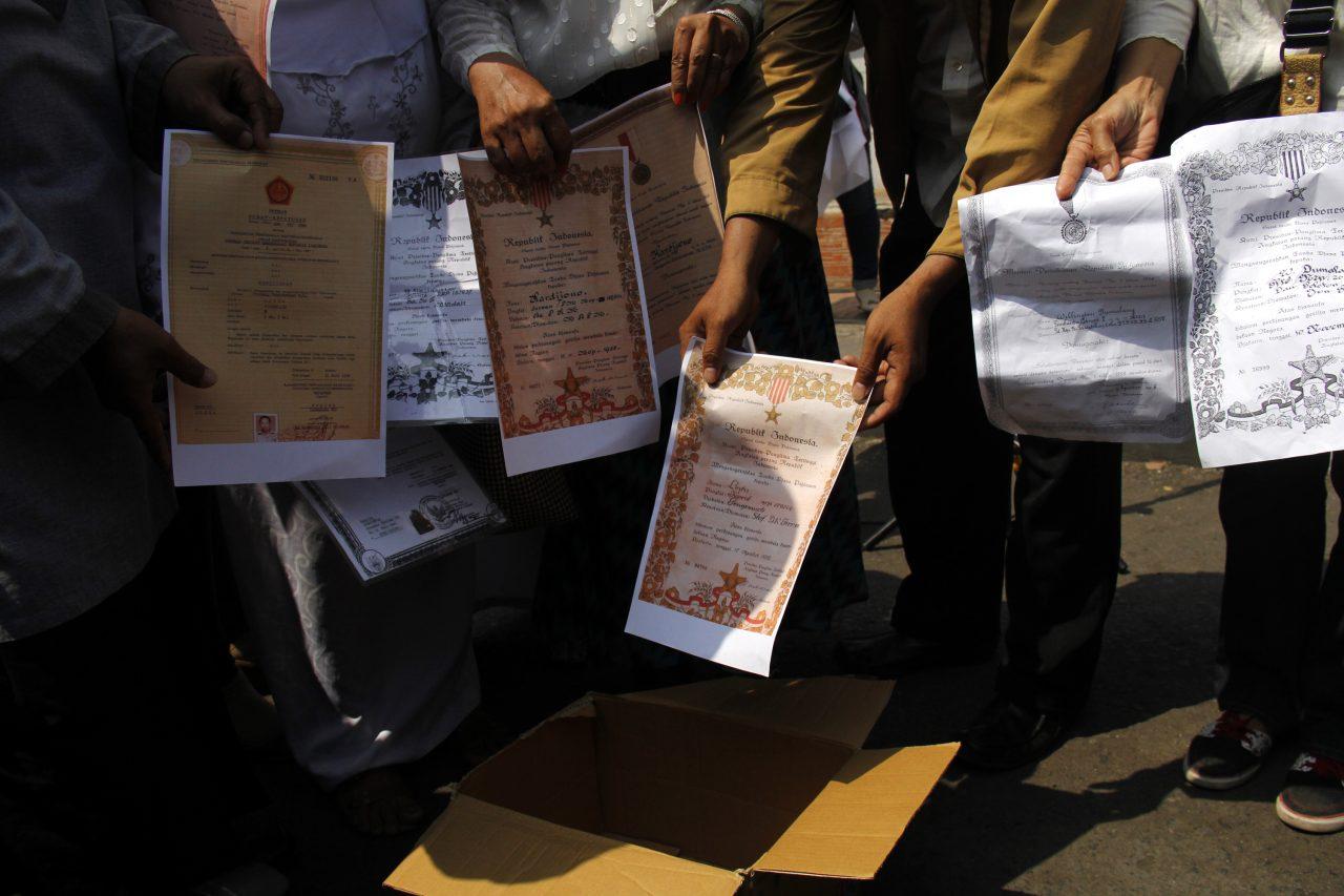 Sejumlah keluarga tentara veteran yang tergabung dalam Forum Penghuni Rumah Negara melakukan pembakaran tanda jasa dari negara saat memperingati hari pahlawan di Monumen Mandala, Makassar, Sulawesi Selatan, Selasa (10/11). Pembakaran tanda jasa dari negara tersebut juga sebagai bentuk penolakan keputusan Pengadilan Negeri Makassar terhadap eksekusi 63 rumah dinas TNI di Makassar. ANTARA FOTO/Abriawan Abhe/nz/15