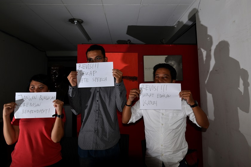 Direktur LBH Pers Asep Komaruddin (kanan), Kepala Divisi Advokasi Hak Sipil dan Politik Kontras Putri Kanesia (kiri), dan Peneliti Pusat Studi Hukum dan Kebijakan Indonesia (PSHK) Miko Susanto Ginting (tengah) memegang sejumlah tulisan yang mengritisi Surat Edaran (SE) Kapolri Nomor SE/6/X/2015 tentang Penanganan Ujaran� Kebencian atau hate speech di kantor Kontras, Jakarta, Selasa (10/11). Surat edaran tersebut dinilai dapat berpotensi dapat mengkriminalisasi seseorang serta membungkam kebebasan berpendapat dan berekspresi. ANTARA FOTO/Rosa Panggabean