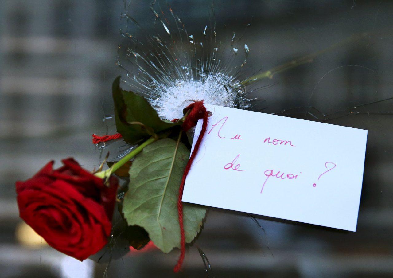 """A rose placed in a bullet hole in a restaurant window the day after a series of deadly attacks in Paris, November 14, 2015. The note reads: """"In the Name of What?"""" REUTERS/Pascal Rossignol TPX IMAGES OF THE DAY *** Local Caption *** Setangkai mawar diletakkan di lubang bekas peluru di jendela restauran sehari setelah serangkaian serangan mematikan di Paris, Sabtu (14/11). Kalimat pada kartu adalah """"Atas nama Apa?"""". ANATRA FOTO/REUTERS/Pascal Rossignol/djo/15"""