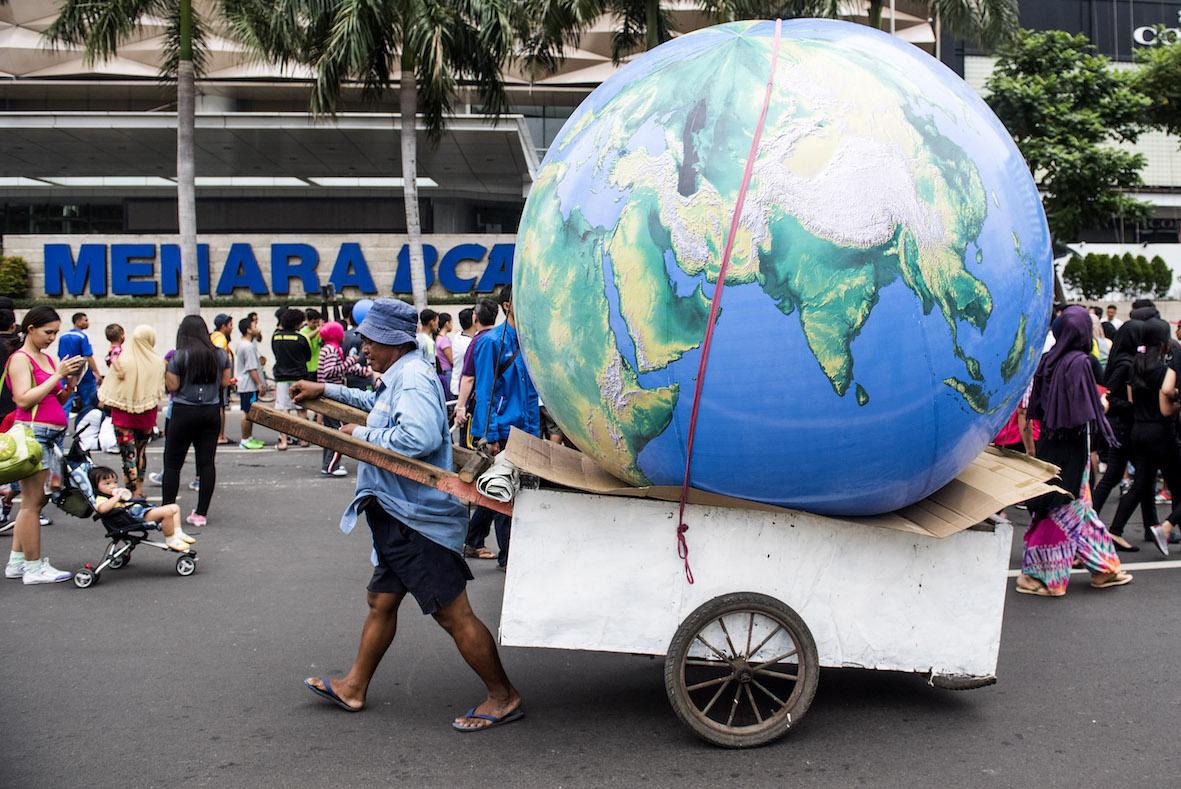 Pegiat lingkungan membawa replika bola dunia sebelum aksi pawai global untuk keadilan iklim jelang pelaksanaan Conference of Parties (COP) ke 21 United Nation Convention on Climate Change (UNFCCC) di kawasan Jalan Sudirman, Jakarta, Minggu (29/11). Aksi tersebut dilakukan untuk menyikapi kondisi iklim dunia yang sudah kritis sekaligus berupa seruan kepada pemimpin negara yang sedang mengikuti konferensi iklim di Prancis. ANTARA FOTO/M Agung Rajasa/kye/15.