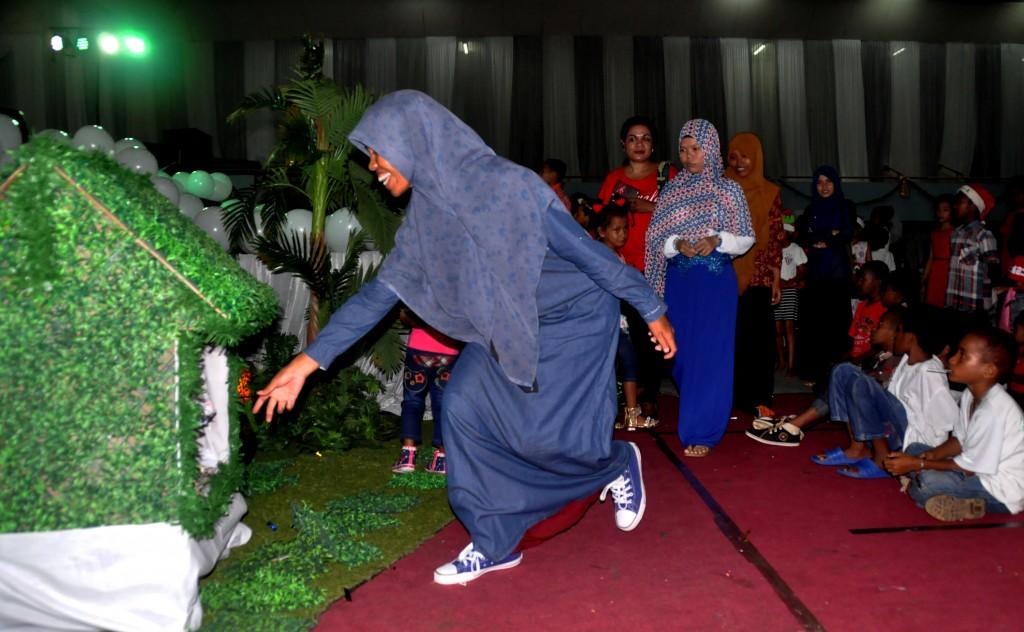 Seorang muslim memasukkan uang ke dalam rumah persembahan pada perayaan Natal Mama dan Anak tahun 2015 di Gedung Olah Raga (GOR) Cenderawasih, Kota Jayapura, Papua, Minggu (20/12). Hadirnya kaum muslim di dalam perayaan tersebut memberi arti toleransi umat beragama yang selalu terjaga dalam setiap kegiataan keagaaman di Papua. ANTARA FOTO/Indrayadi TH/aww/15.