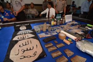 Sejumlah perwira polisi berada di dekat barang bukti hasil penyisiran aparat di Kabupaten Poso yang digelar di Mapolda Sulawesi Tengah di Palu, Kamis (31/12). Barang bukti dengan atribut yang jelas tersebut menunjukkan adanya jaringan Islamic State of Iran and Suriah (ISIS) yang beroperasi di daerah bekas konflik horizintal itu. ANTARA FOTO/Basri Marzuki/
