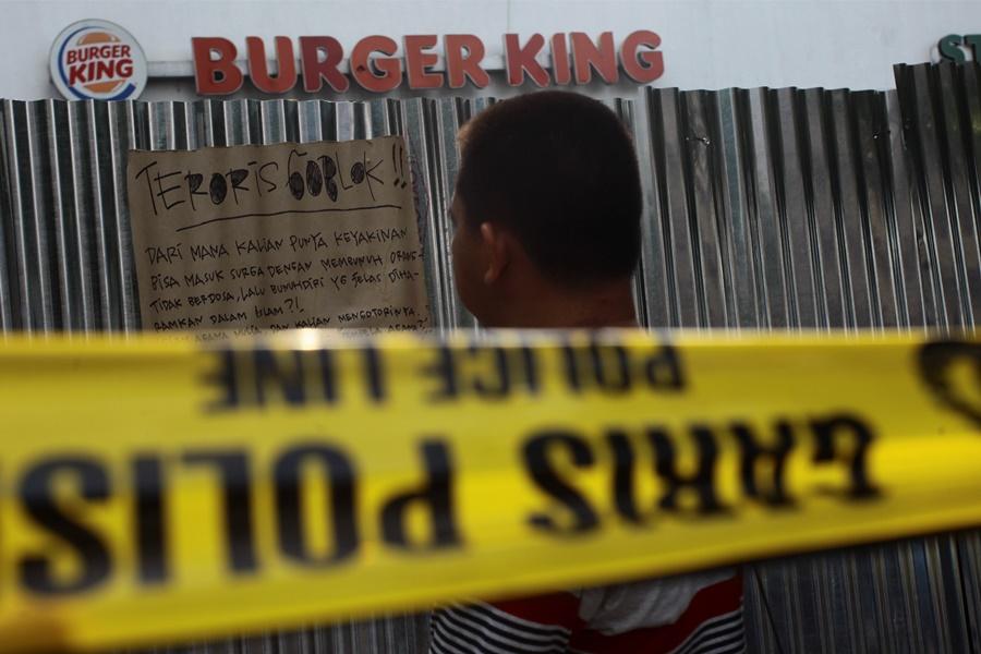Warga melintas di depan restoran Burger King pasca penyerangan teroris di pos polisi dan sejumlah gedung di Sarinah Thamrin Jakarta, Jumat (15/1). Serangan teroris pada Kamis (14/1) tersebut mengakibatkan beberapa tempat dan kendaraan mengalami rusak berat . ANTARA FOTO/Muhammad Adimaja