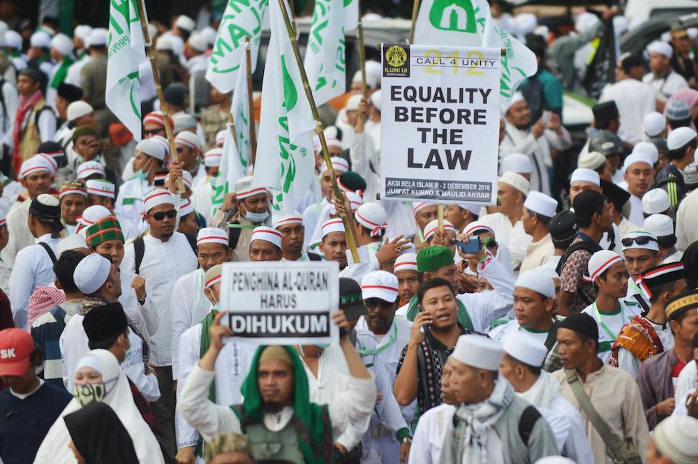 Sejumlah peserta aksi membawa poster saat long march menuju Monas untuk mengikuti aksi 212 atau 2 Desember di Jalan MH Thamrin, Jakarta, Jumat (2/12). Aksi tersebut untuk mendesak pihak terkait agar segera menuntaskan kasus dugaan penistaan agama. ANTARA FOTO/Akbar Nugroho Gumay/aww/16.