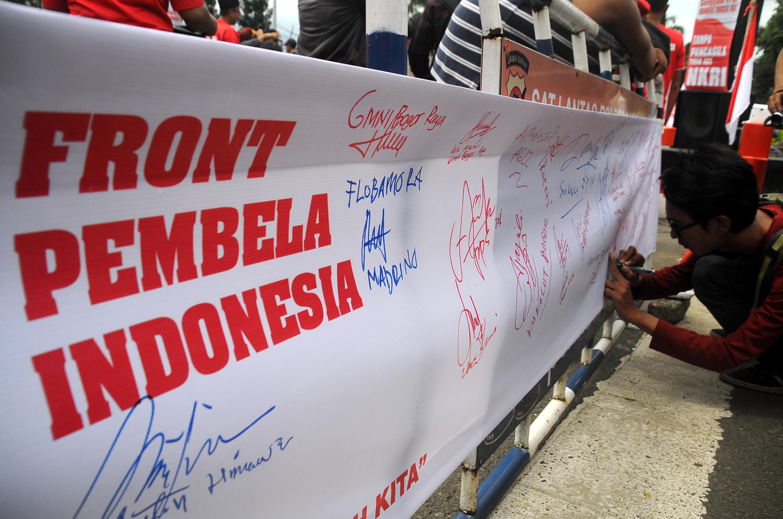 Massa membubuhkan tanda tangan dalam aksi mendeklarasikan kebhinekaan Indonesia di Tugu Kujang, Kota Bogor, Jawa Barat, Kamis (24/11). Berbagai elemen masyarakat meleburkan diri dalam wadah Front Pembela Indinesia (FPI) mengumandangkan ke-bhinekaan dari Kota Bogor, dalam aksinya mereka menolak aksi yang ingin mengubah dasar negara dan makar. ANTARAFOTO/Yulius Satria Wijaya/pd/16.