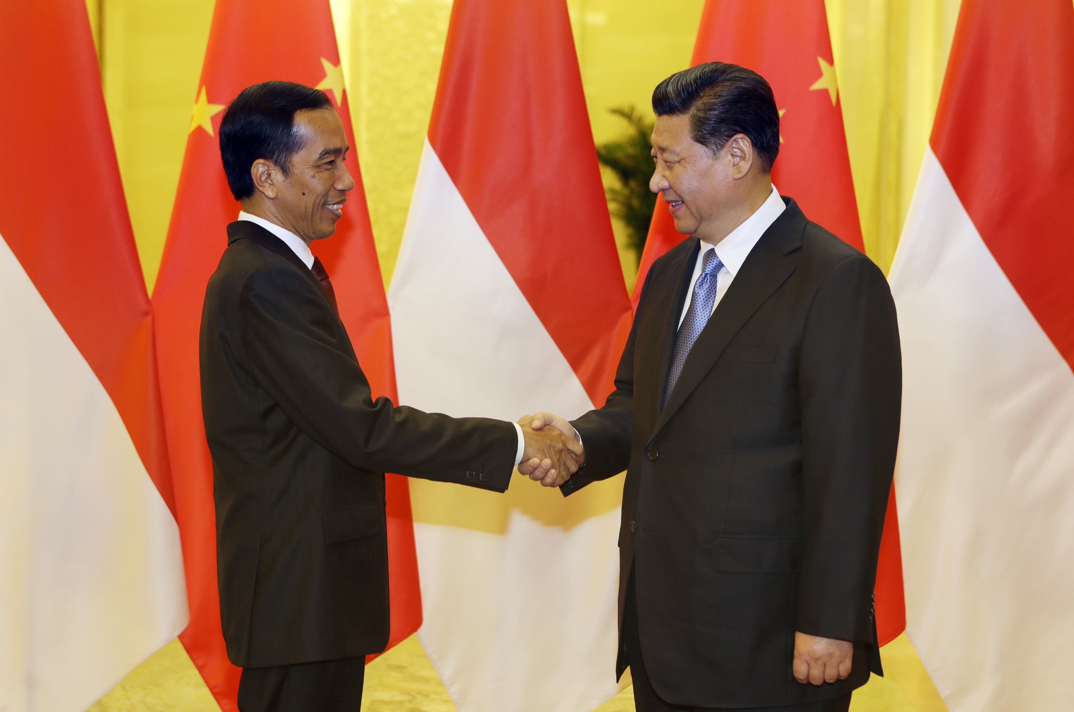 Indonesia's President Joko Widodo (L) shakes hands with China's President Xi Jinping before their meeting at the Great Hall of the People in Beijing on November 9, 2014. The Indonesian leader is in the Chinese capital to attend the Asia-Pacific Economic Cooperation (APEC) Summit leaders' meeting. AFP PHOTO / POOL / Jason Lee