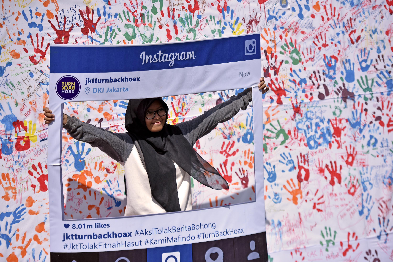 Seorang warga berfoto usai membubuhkan cap tangan ketika kampanye sekaligus deklarasi masyarakat Indonesia anti 'hoax' di Kawasan Jalan MH Thamrin Jakarta, Minggu (8/1). Kampanye anti hoax (berita bohong) itu untuk mengajak masyarakat agar memakai media sosial secara positif dan tidak menyebarkan berita palsu. ANTARA FOTO/Wahyu Putro A/foc/17.