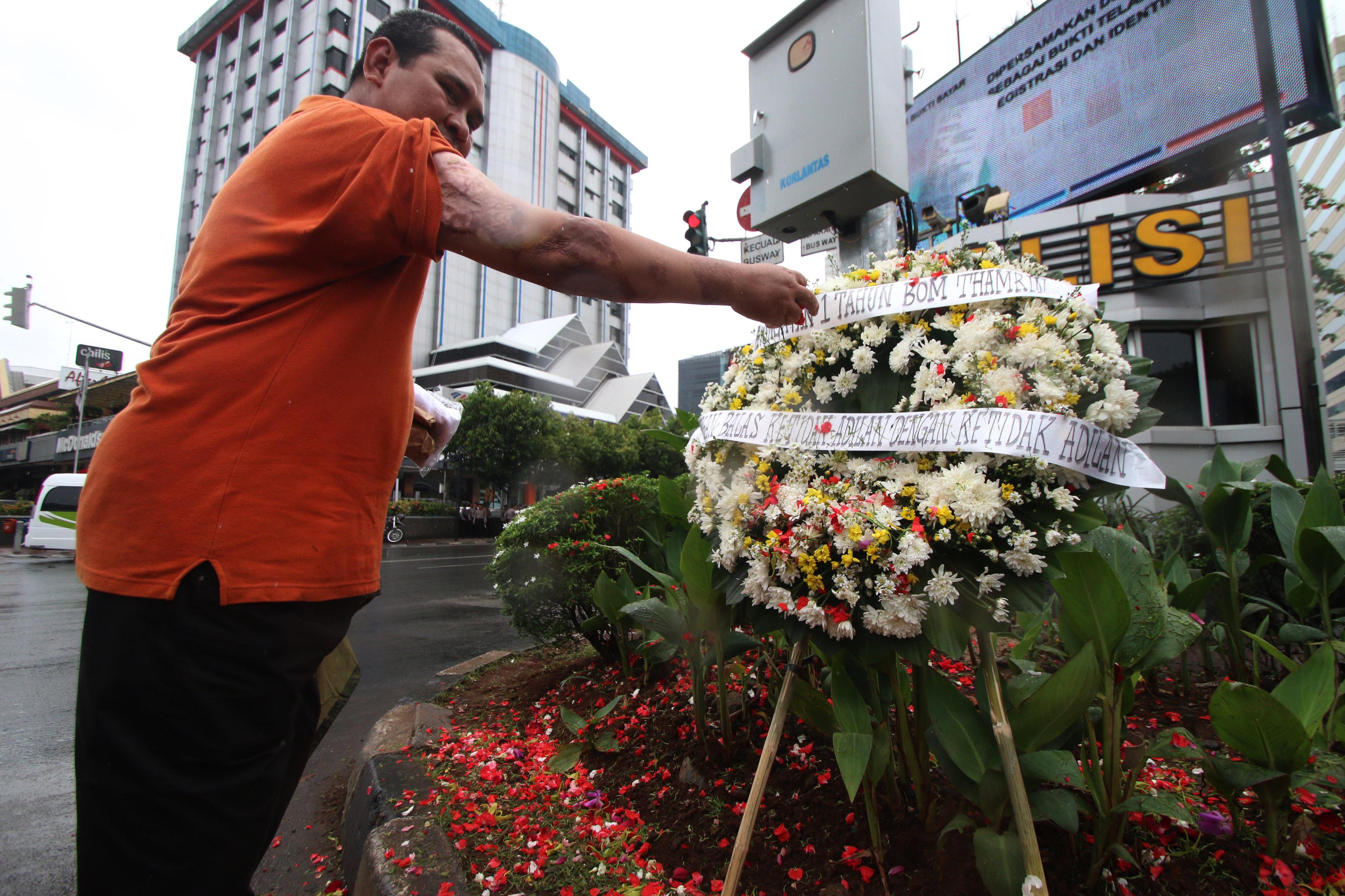 """Korban serangan """"Bom Thamrin"""" yang merupakan anggota kepolisian, Aiptu Denny Maheu, melakukan tabur bunga di lokasi kejadian di Jalan MH Thamrin, Jakarta, Sabtu (14/1). Aksi tabur bunga dilakukan dalam rangka memperingati satu tahun kejadian aksi terorisme """"Bom Thamrin"""". ANTARA FOTO/Rivan Awal Lingga/kye/17"""