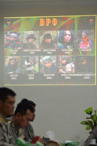 Sejumlah perwira polisi berada di depan slide yang menampilkan sisa Daftar Pencarian Orang (DPO) Teroris Poso di Mapolda Sulawesi Tengah, di Palu, Sabtu (31/12). Polda Sulteng merilis, jumlah DPO Teroris Poso yang sebelumnya 41 orang, kini tersisa 9 orang dan masih berkeliaran di hutan-hutan Poso, selebihnya sebanyak 20 orang tewas tertembak dan dua orang tertangkap. ANTARAFOTO/Basri Marzuki/foc/16.