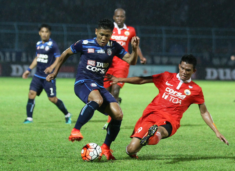 Pesepakbola Arema FC Ahmad Bustomi (kiri) berusaha mempertahankan bola dari hadangan pesepakbola Persija Jakarta, Sandi Darma Sutte (kanan) dalam pertandingan Piala Presiden di Stadion Kanjuruhan, Malang, Jawa Timur, Sabtu (11/2). Pada akhir babak pertama Persija mengimbangi arema dengan skor 1-1. ANTARA FOTO/Ari Bowo Sucipto/ama/17.