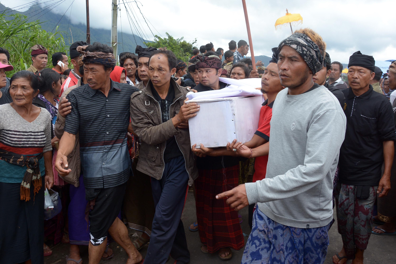 Sejumlah warga mengangkat peti jenazah korban longsor di Desa Songan, Kintamani, Bali, Senin (13/2). Sebanyak tujuh korban dari 13 warga yang meninggal akibat bencana longsor di Desa Songan, Kintamani, pada Kamis (9/2) tersebut baru bisa dikebumikan karena masih mencari hari baik sesuai aturan dan kepercayaan adat setempat. ANTARA FOTO/Wira Suryantala/pd/17.